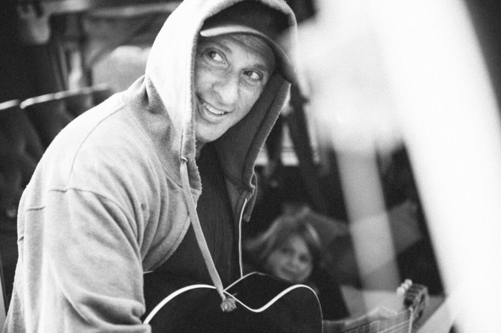 Dan Bern wearing a hoody and playing guitar